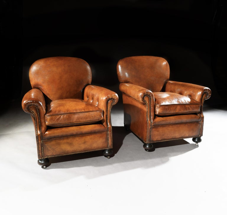 A fine pair of antique leather club chairs raised on turned front bun feet, of very good proportions and extremely comfortable.