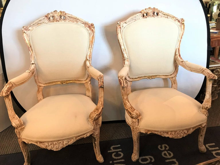 A pair of antique Louis XV style armchairs in painted distressed frames. Each having a wonderful antique frame that has been washed with new burlap upholstery. Lxx.