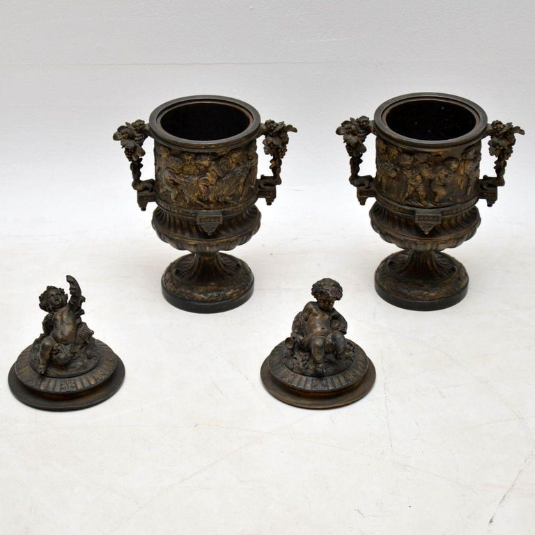 Pair of antique classical bronze urns and lids with well cast decoration depicting many cherubs, grape vines and other classical items. The lids have very detailed well defined cherubs. These urns were originally gilded and there is some gilding