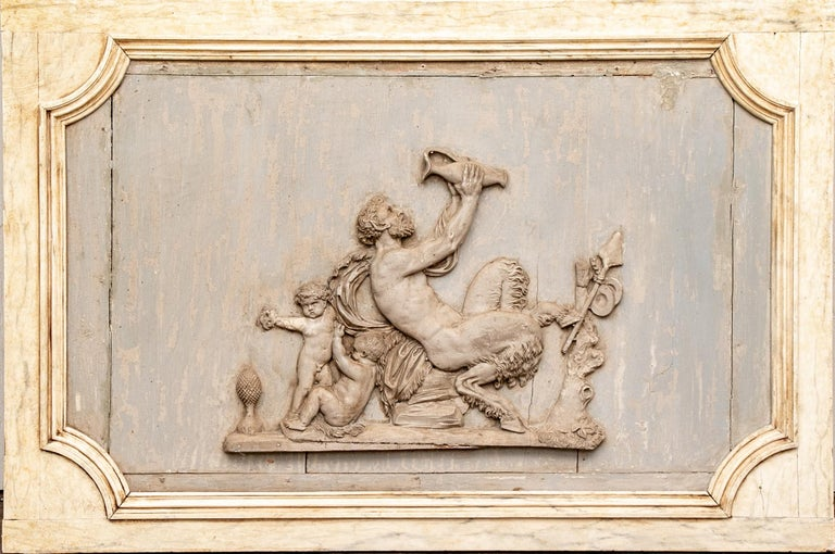 Rare and decidedly spectacular early pair of neoclassical plaques. One having a carved and painted Bacchic relief plaque with putti joining Pan drinking from a jar. The antique plaques mounted in pale yellow faux marble painted wood frames. The