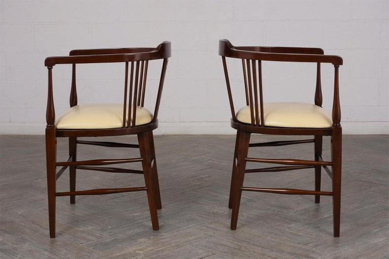 This Pair of Antique English Regency Style Armchairs is made out of solid mahogany wood. It features its original rich dark walnut finish, inlay design, and curved backrest. The armchairs also have a newly upholstered leather seat in a cream color