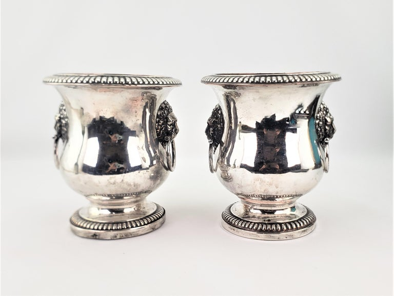 This pair of antique early Sheffield plated wine coolers are signed by and unknown maker and originated from England from approximately 1800 in a period Georgian style. The wine coolers have applied and plated figural lion mounted handles with