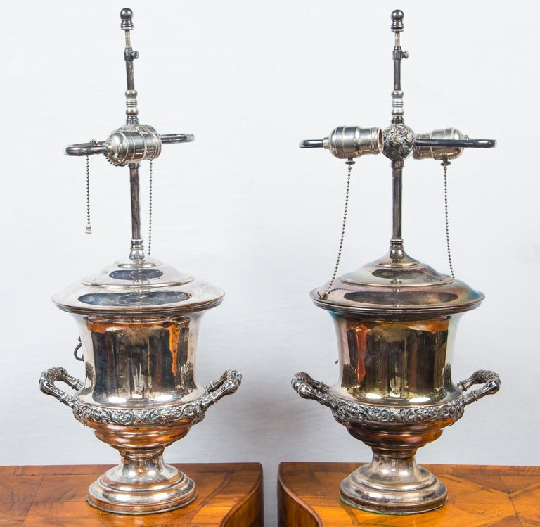 Each has been converted to table lamps, with a wire coming through the lid of the urn. Bleeding of silver, exposing the copper underneath. Unmarked. Decorative bands of grapes, grape leaves and vines.  The width from handle to handle is 9 inches.