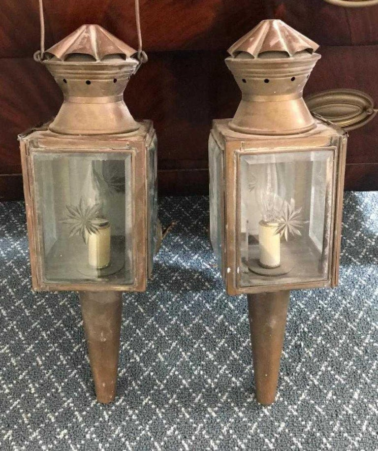 The pair of antique copper carriage or coach lights have been converted to electrified wall sconces, once the property of an historic Hudson River Valley mansion. The bevelled glass windows are decorated with etched or cut glass star-pattern