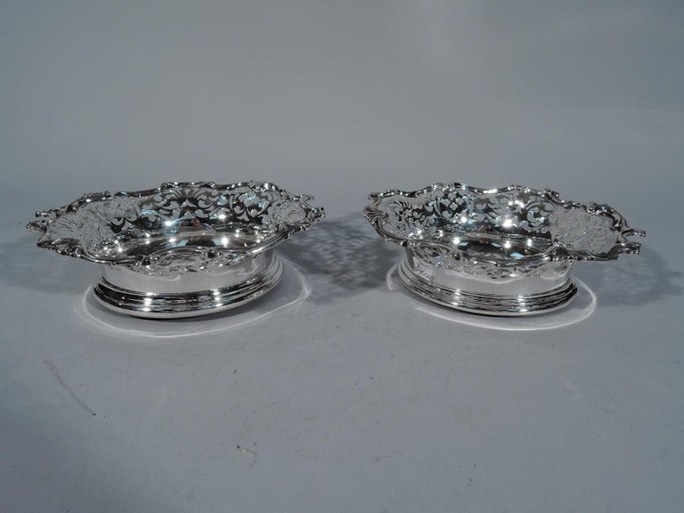 Pair of Victorian sterling silver wine bottle coasters. Made by Howard in New York in 1888. Each: Solid well with engraved armorial. Sides have pierced scrollwork, and rim has applied scrolls and leaves. Mounted to felt-lined wood. Fine pieces by a