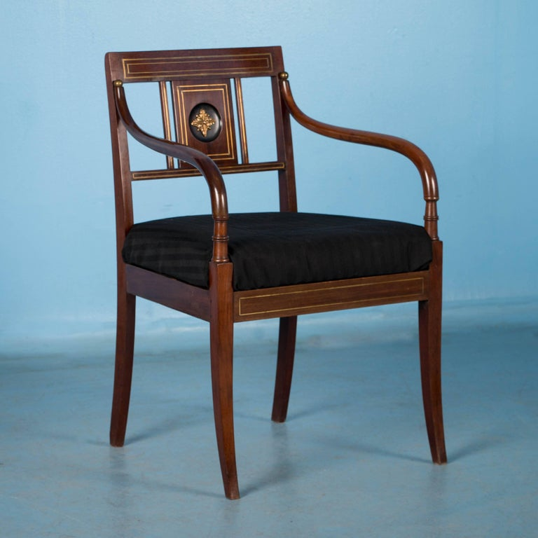 This exceptional pair of Empire period mahogany armchairs are from Stockholm, Sweden. Note in the close up photos the brass inlay and medallion in the center panel of the back adding to the elegant appeal of the pair. Both chairs have been restored,