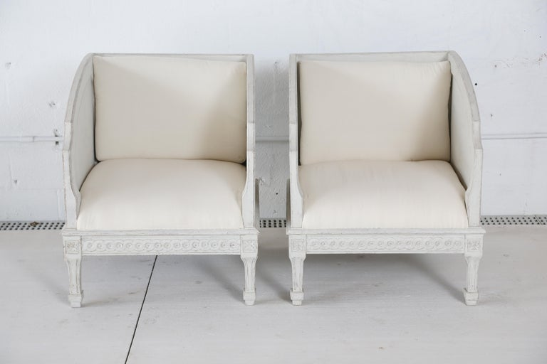 Pair of antique Swedish painted wood frame and carved bergère chairs, with natural muslin upholstery,