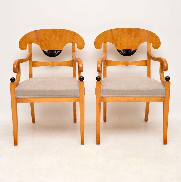 These are one of the nicest pairs of Swedish antique Biedermeier armchairs I've had. The wood is satin birch and is a wonderful blond color. They have Trafalgar backs, scroll over arms, wide newly upholstered seats and sit on sabre legs. There is a