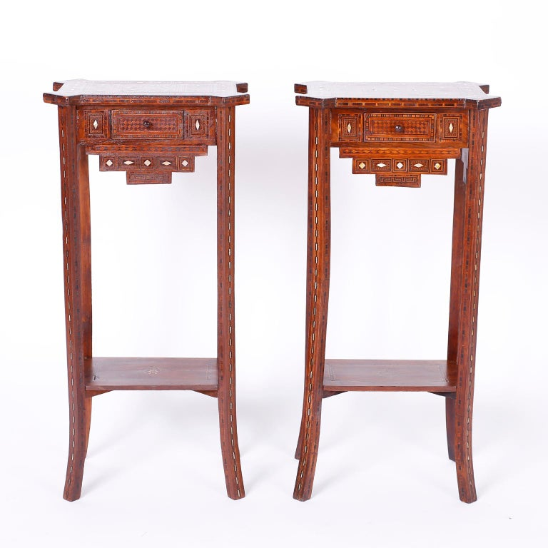 Refined pair of Syrian one drawer tables or stands with a tall, elegant form crafted in walnut and inlaid from top to bottom with geometric designs using mother of pearl, mahogany, ebony, and king wood featuring splayed legs and a desirable slim