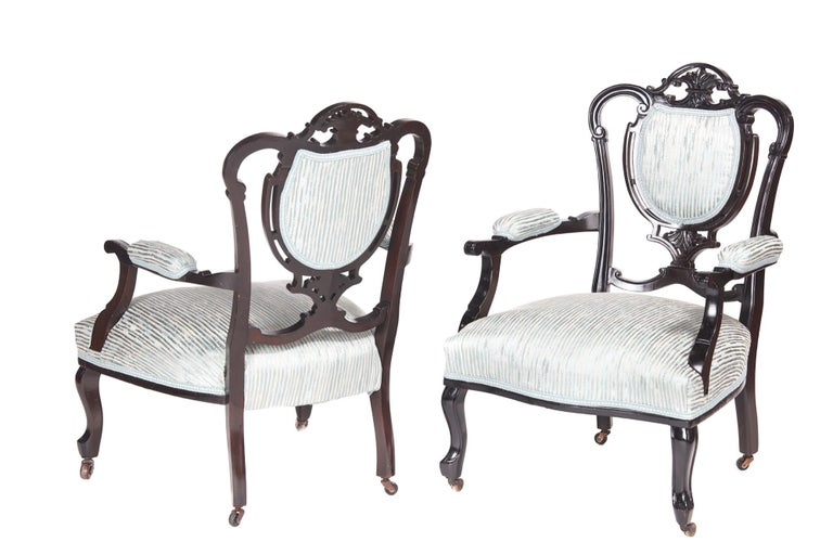 Pair of antique 19th century Victorian carved black lacquered library chairs, with lovely carved and shaped backs, shaped open arms, standing on cabriole legs to the front and out-swept legs to the rear. They have the original castors and have been