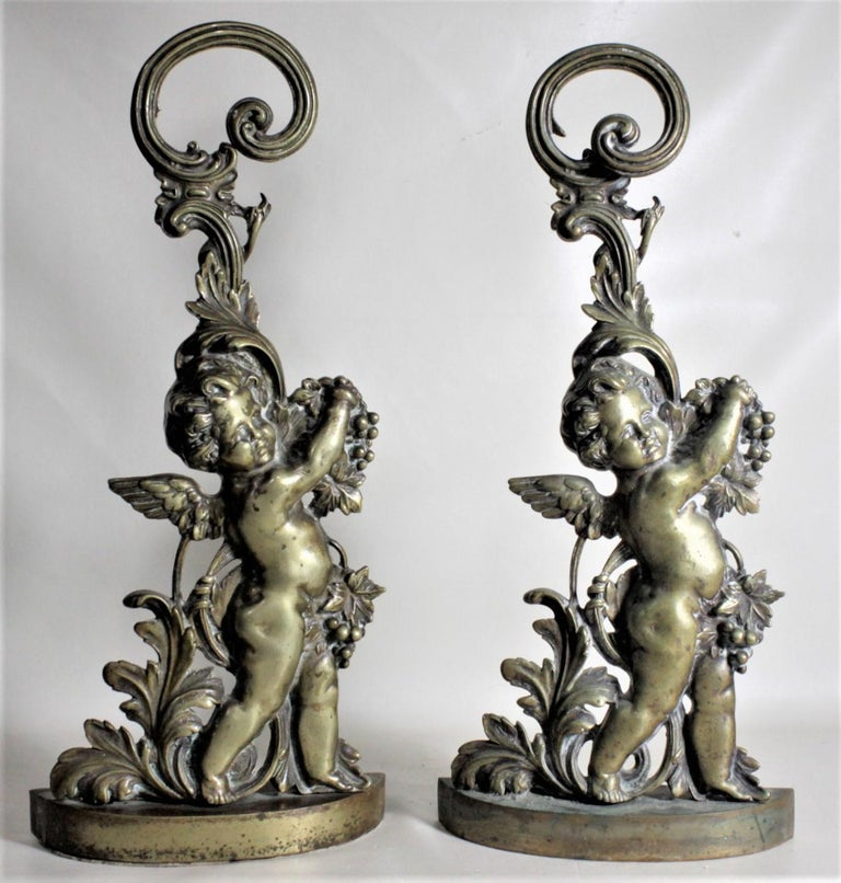 This pair of antique detailed cast brass figural cherub door stops are unsigned, but presumed to have been made in the United States in circa 1880 in the period Victorian style. These door stops each show a nicely executed cast brass figural cherub
