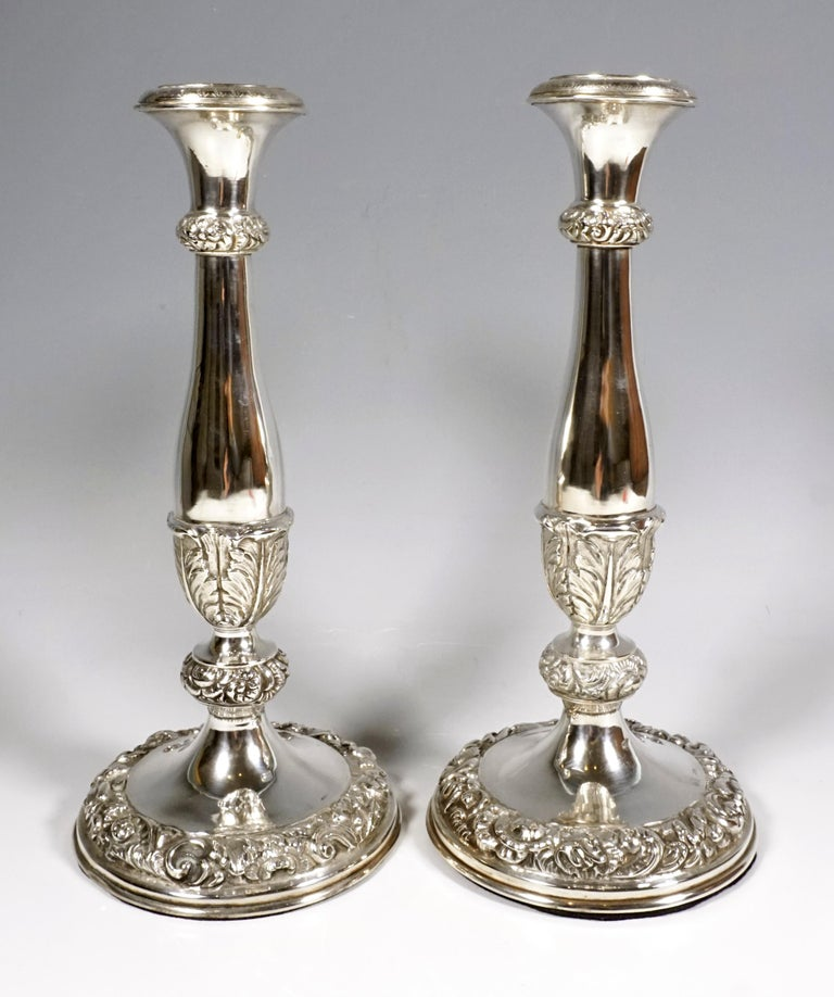 Two baluster-shaped candleholders on a round, broad base, smooth finish with embossed and chased flower, leaf tendril and rocailles decoration on the base and bulge rings, achantus leaves on the lower part of the shaft, slightly flared vase-shaped