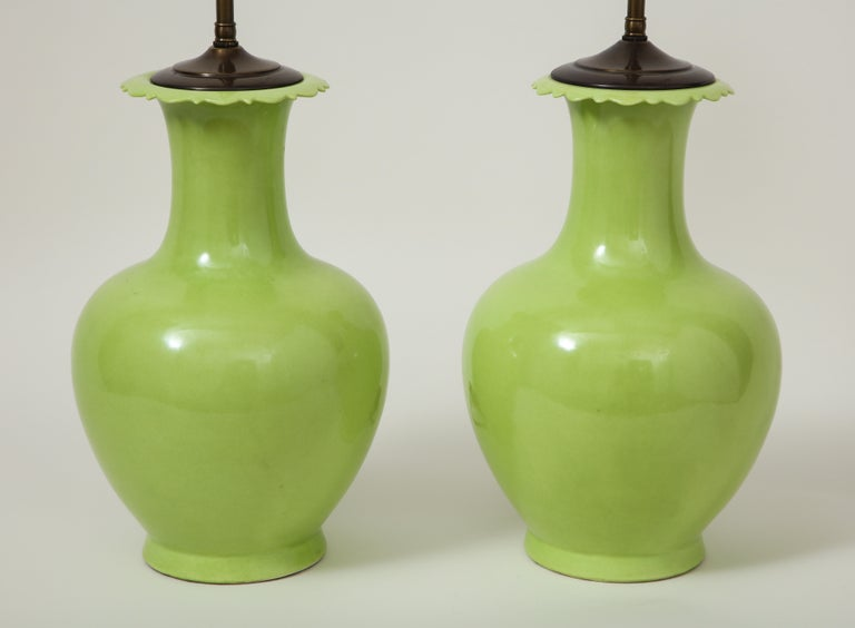 Each of baluster form with scalloped rim, fitted with an adjustable rod and two-light sockets. Height to top of vase is 14.75