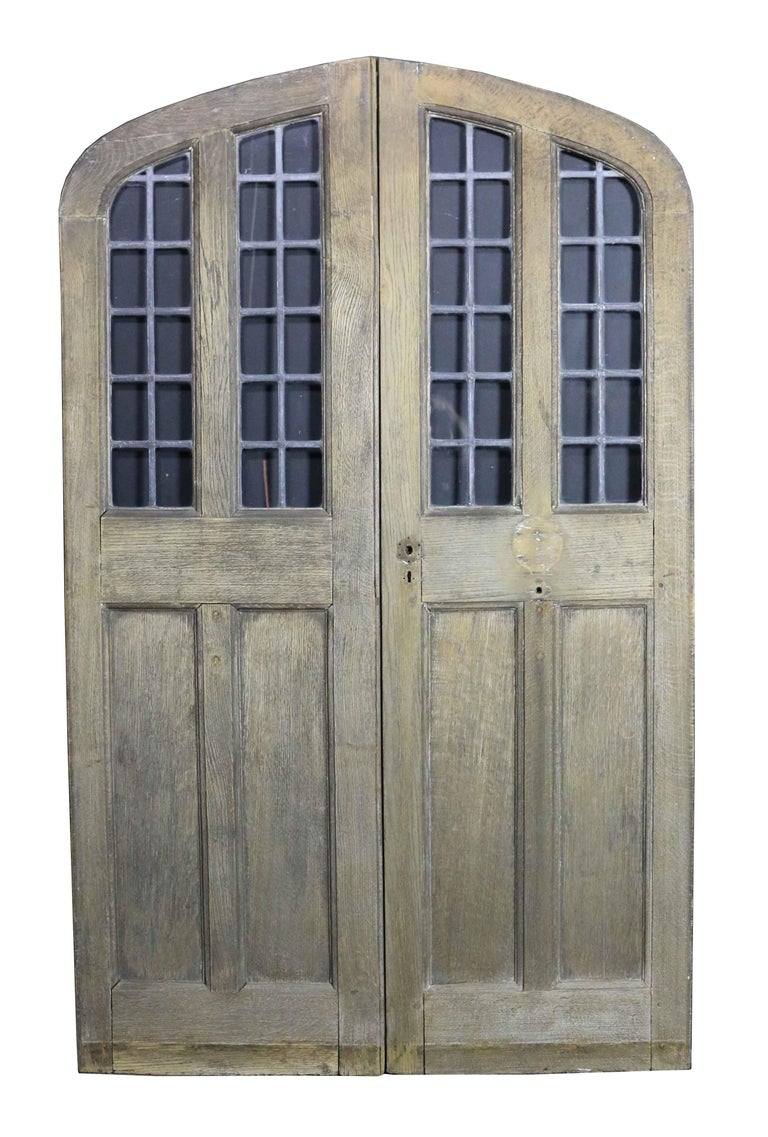 Pair of arched oak double doors with leaded glass panel, circa 1900. Please note that the glass is not insured in transit outside of the UK.