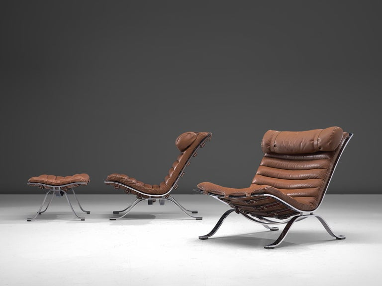 Arne Norell for Norell Møbel AB, pair 'Ari' lounge chairs with ottoman, brown leather, chrome-plated steel, Sweden, 1966.  This pair of lounge chairs with pouf are designed by Arne Norell. The whole frame is executed in chrome-plated steel, and