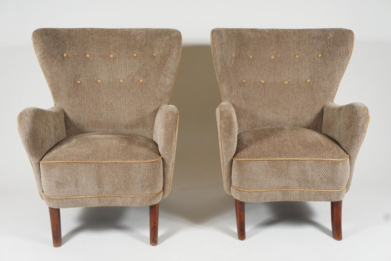 A pair of Danish modern armchairs by Danish designer Alfred Christensen. These are a contrast to his well-known 'open arm' armchairs in that they are fully upholstered. Very comfortable, high backed with exaggerated arms, newly upholstered in a