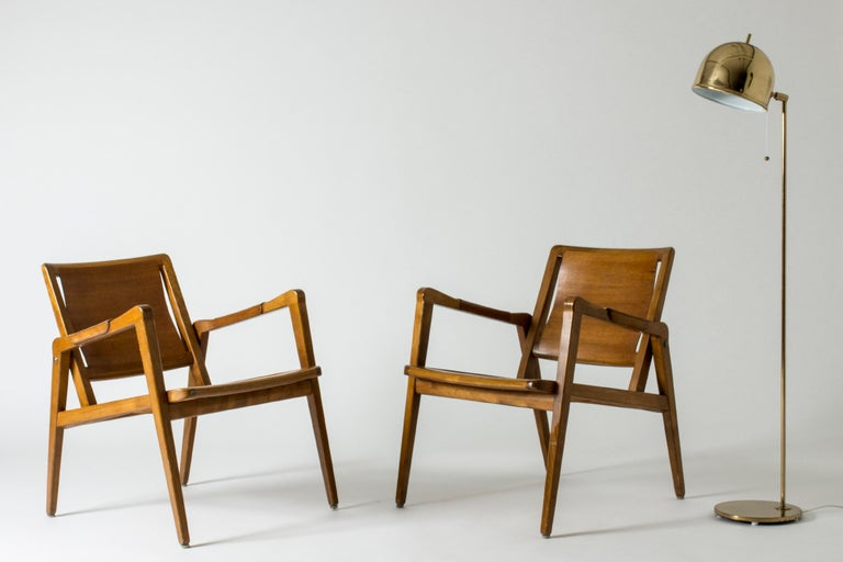 Pair of rare lounge chairs by Axel Larsson made entirely from wood in a warm color. Casually elegant design. The seats and backs follow the form of the body, neat wooden details on the armrests.  Measure: Seat height 40 cm.