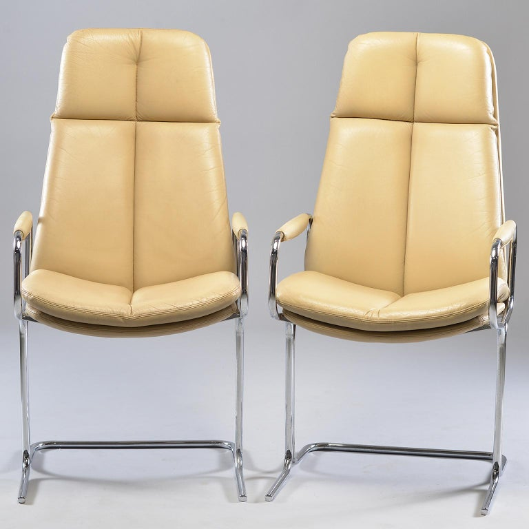 Pair of armchairs designed by Tim Bates for the Eleganza collection at Pieff, circa 1970s. Frames are made of tubular metal with chrome finish. Seats are ivory colored leather with high backs, slightly curved seats and padded armrests. Very good