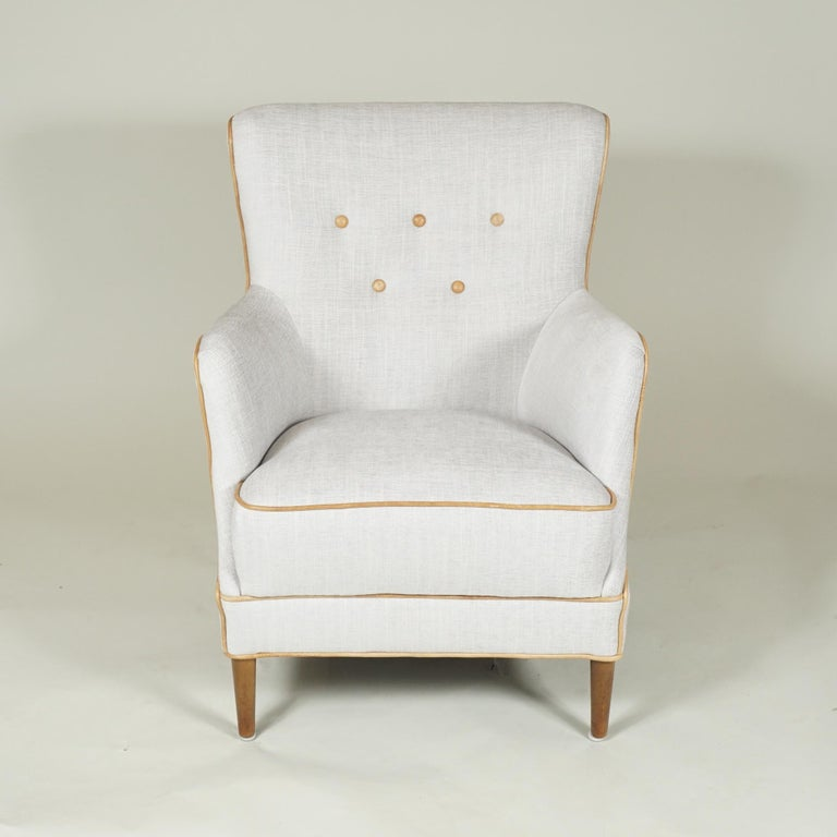 Comfortable pair of easy armchairs from 1950s Denmark, solidly built and recently recovered in antique white cotton with beige buttoning and trim in leather.