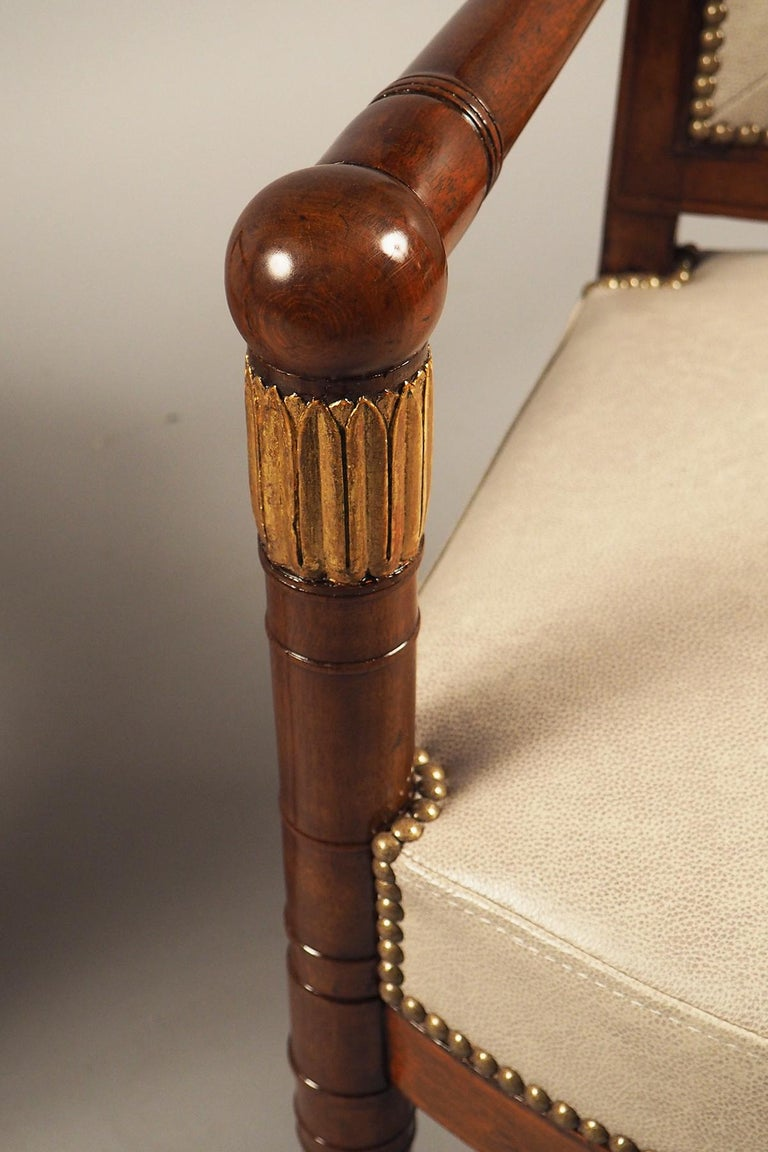 Partially gilded walnut structure featuring turned armrests and front legs, upholstered in Spinneybeck leather decorated with nailheads.