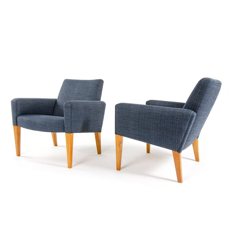 A pair of lounge chairs, newly upholstered in a dark blue, cotton and linen weave, on top of tapered wood legs. Designed by Hans Wegner, made by AP Stolen in Denmark, circa 1950s.