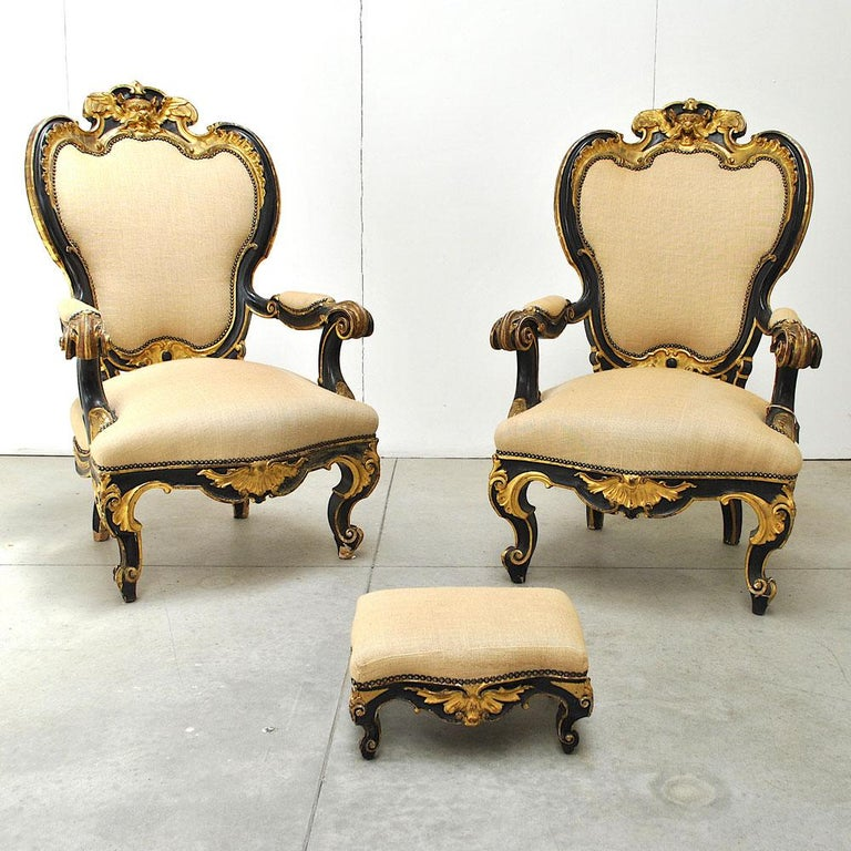 Powerful pair of armchairs, with a small ottoman, from the mid-19th century in black lacquer and pure gold worked in agate stone, precious Venetian manufacture. Ottoman pouf size is in cm H 20, P 29, L 38.