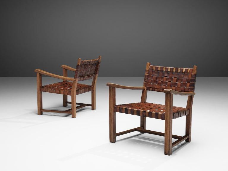 Pair of armchairs, cognac leather, solid oak, Europe, 1960s  Pair of wonderful armchairs in solid oak. These armchairs have rustic appearance with their sturdy oak frames. The armrests are slightly curved with rounded edges. Notable is the grain of