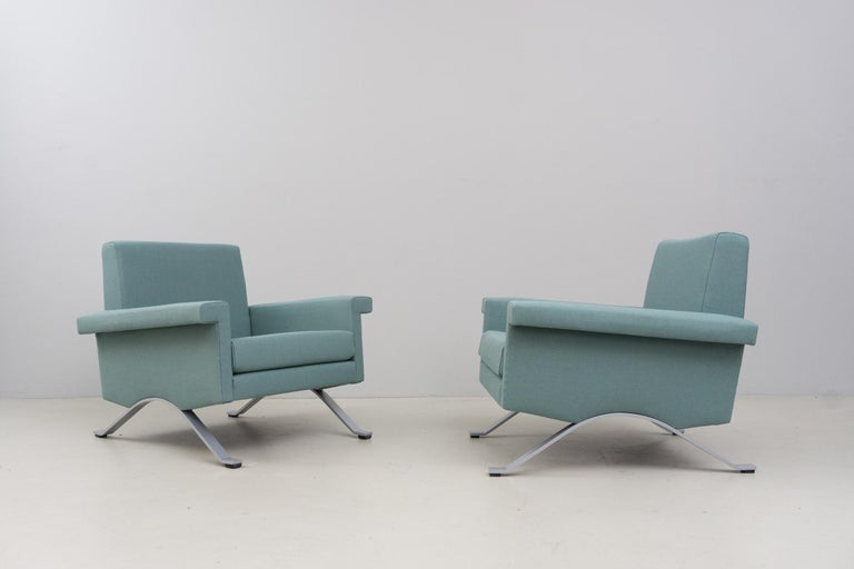 These very elegant and minimal, precise armchairs have a matt chromed metal structure and new upholstery and cover. The cover is made of 100% wool in a cool grayish green. Excellent condition.  The last production of this piece was manufactured in