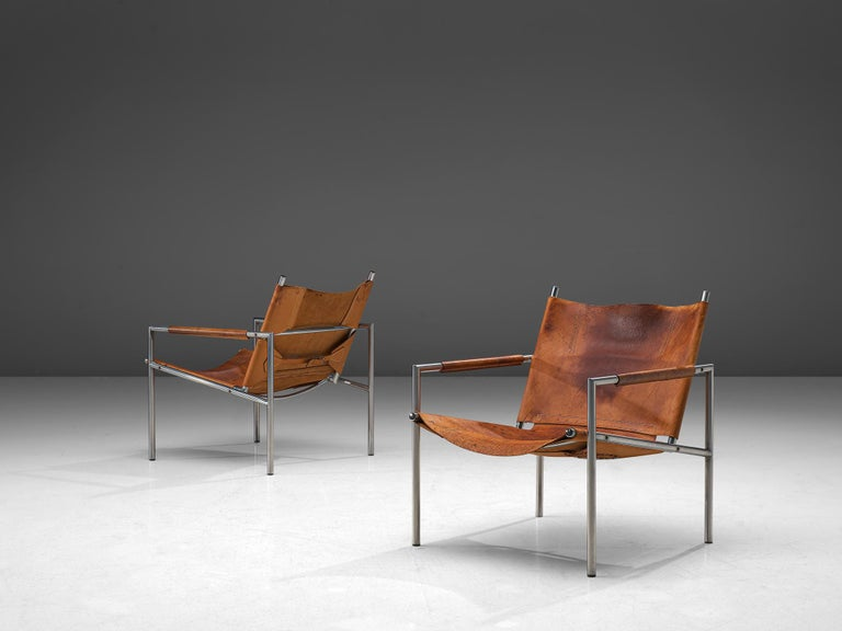 Martin Visser, pair of armchairs, leather and metal, The Netherlands, 1965.  These modern, Minimalist easy chairs are made of a tubular brushed steel in combination with soft, patinated cognac leather upholstery. The armrests are covered in cognac