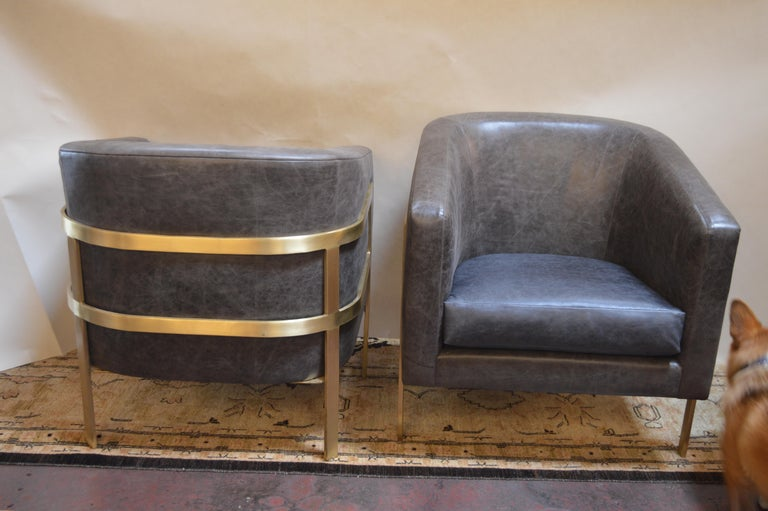 Two distressed grey leather armchairs with dark blue leather seats and polished brass frame. In the style of Milo Baughman.