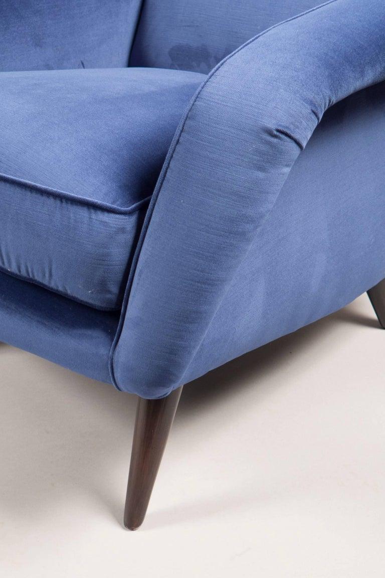 Over-upholstered chairs, each with a steeply reclined back, down curved arms and four tapered tinted wooden legs.  Measure: Seat height 16