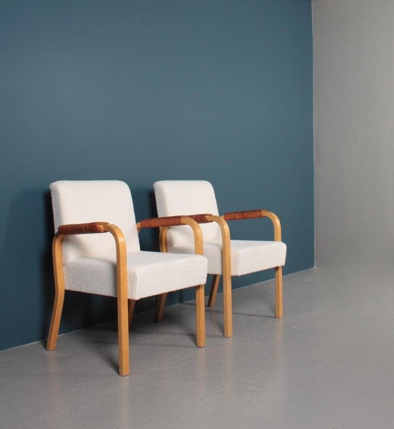 Pair of armchairs with bouclé fabric and patinated leather arms. Designed by Alvar Aalto in 1947 for Artek. Great condition.