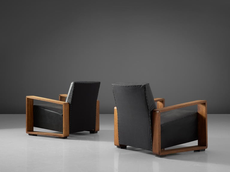 Set of two lounge chairs, in stained beech and black leather, Czech Republic, 1950s. 