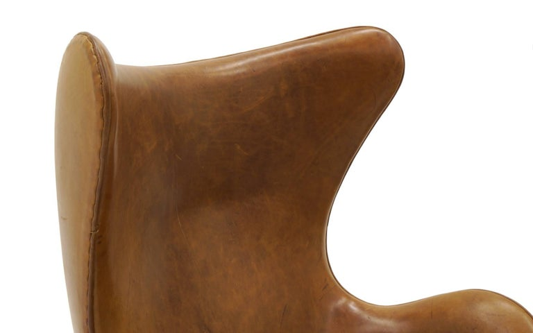 pair of arne jacobsen egg chairs in cognac tan leather made by