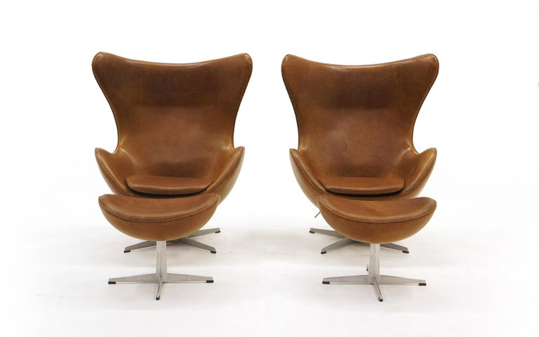 Pair of swivel tilt egg chairs and ottomans designed by Arne Jacobsen and manufactured by Fritz Hansen, Denmark. Jacobsen's modern take on the wingback lounge chair. The tilt mechanism is adjustable. The set is from the early 2000s and have been