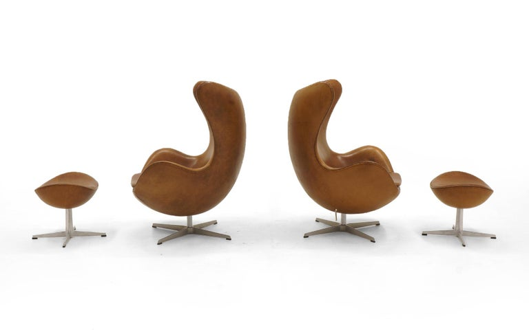 Mid-Century Modern Pair Arne Jacobsen Egg Chairs with Ottomans, Cognac Leather. Price is for all.