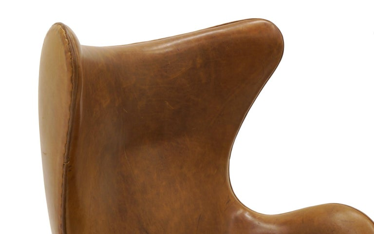 Contemporary Pair Arne Jacobsen Egg Chairs with Ottomans, Cognac Leather. Price is for all.
