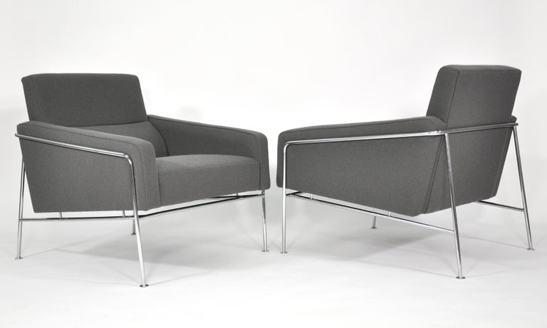 Iconic pair of vintage midcentury armchairs from the 3300 series designed by Arne Jacobsen in 1956 and manufactured in Denmark by Fritz Hansen. The bucket style seats appear to float within a thin and clean-lined chrome frame. The chairs feature a