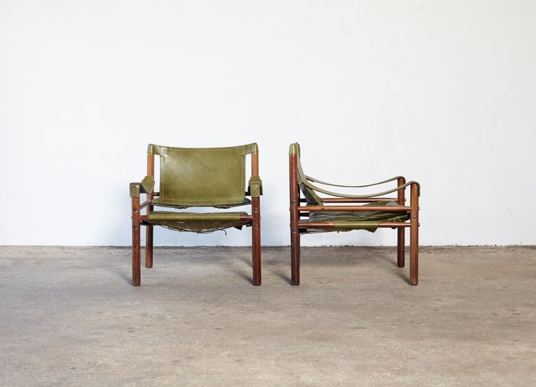 A rare authentic pair of original Arne Norell safari sirocco chairs, rosewood frames and patinated green leather.  Made by Norell Mobler in Sweden (1970s) with makers label intact.      Fast and inexpensive shipping worldwide.  The chairs will need