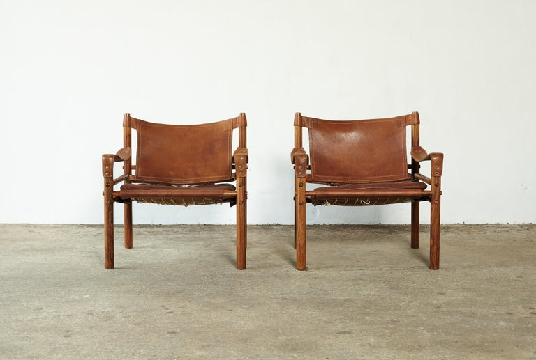 A super pair of authentic vintage Arne Norell safari sirocco chairs in rosewood and patinated brown leather. Made by Norell Mobler in Sweden. Very good original condition. 