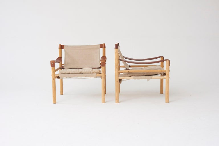 A pair of beautiful Arne Norell safari sirocco chairs in ashwood and canvas. Made by Norell Möbel AB, in Sweden with makers label intact. Very good vintage condition. Linen/canvas recently re-upholstered, slight variation in color tone between