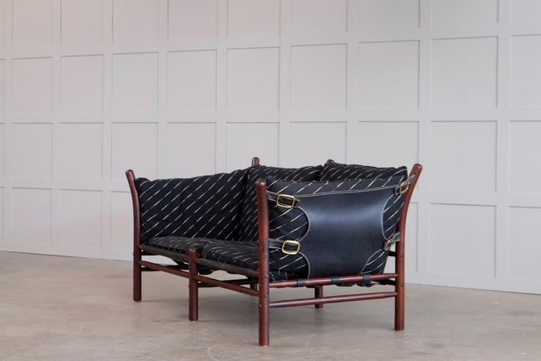 Pair of Ilona sofas designed by Arne Norell 1960s, produced by Norell Möbel AB, Sweden. Dark stained beech, fabric, leather and brass details. Please note: Listed price is for 1 sofa. Global front door shipping, delivery within 14 days: €499/each.