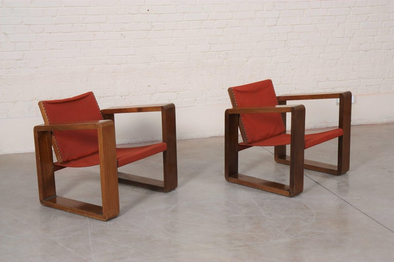 Mahogany, profiled frames forming legs and armrests. Seat and backrest composed of a stretched canvas of red color. Swivel backrest.