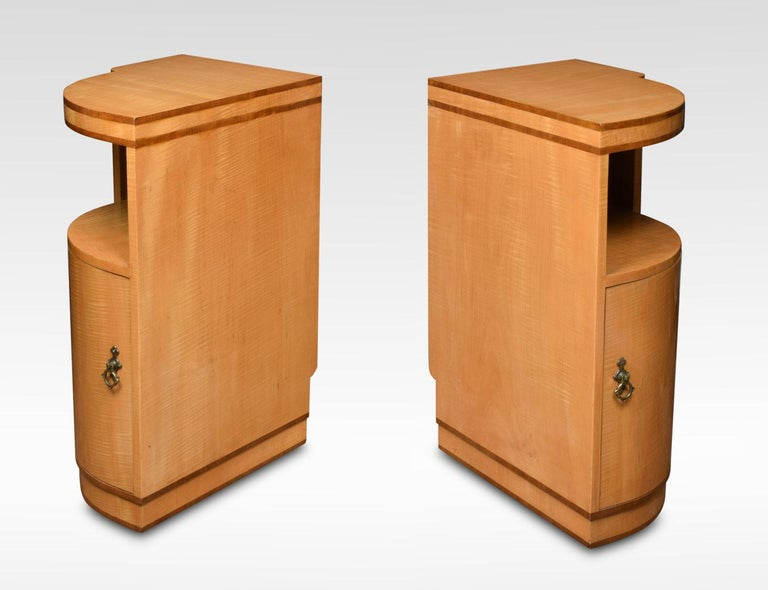Pair of Art Deco maple and walnut banded bedside cabinets. Having curved fronts with single door opening to reveal single fixed shelf all raised up on shaped plinths. Dimensions: Height 30 inches Width 14 inches Depth 20 inches.