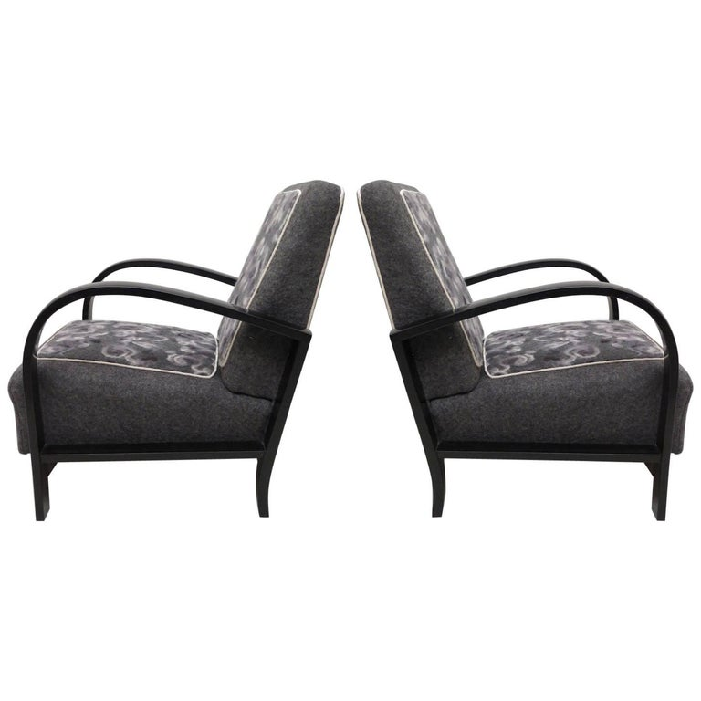 Pair of Italian Art Deco armchairs, embellished with a fabric insert from an important Italian silk factory.  The wooden frame, armrests and lower part, are completely polished in black shellac; while the seat and backrest, are covered with a gray