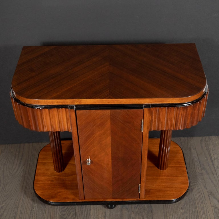 This stunning pair of Art Deco Machine Age end tables or nightstands were realized in the United States circa 1935. They feature skyscraper style walnut tops (with black lacquer banding) whose grain has been bookmatched to create a stunning