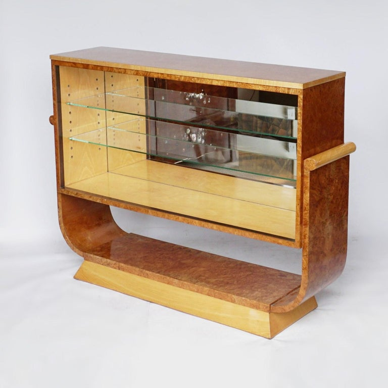 A pair of Art Deco bookcases by Harry & Lou Epstein. Burr walnut and satin birch veneers with a macassar ebony banding. Mirrored lit interior with two glass shelves. Set over a U-shaped base.  Dimensions: H 95cm, W 130cm, D 32cm  Origin: