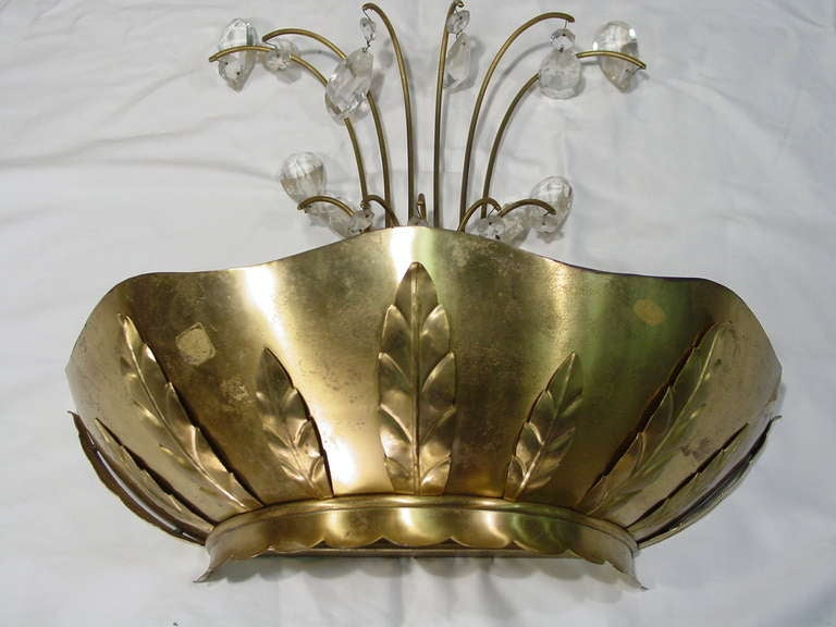 A pair of Art Deco brass palm wall sconces with decorative arms and ornamental crystals. The wall-mounted fixtures feature scalloped edges.