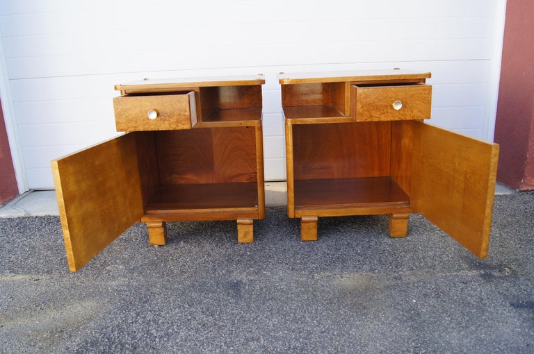 This lovely pair of 1930s Art Deco nightstands features mirror-image glossy burl wood cases on sturdy carved legs. Behind a door is a large storage space; above is a small drawer opposite an open shelf. Brass accents decorate each corner of the top