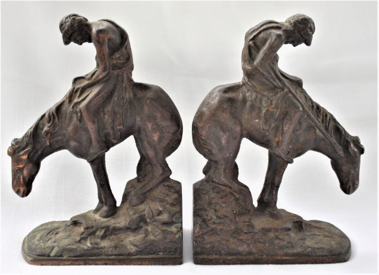 This set of cast and bronze finished metal sculptural bookends were made in 1928, presumably in the United States, in the American Colonial style. Each bookend does have a manufacturer's mark cast into it in a bottom corner, but deemed illegible and